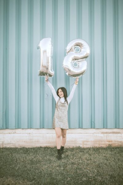 A teen girl holding up an 18 shaped balloon.