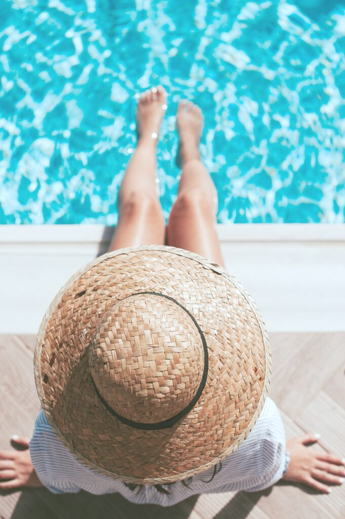 A woman sits by the edge of a pool. It's a top view of her, only her hat, and legs dipped in the pool are seen.