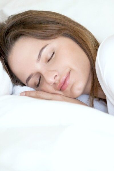 A woman sleeps peacefully on a white pillow and sheets.