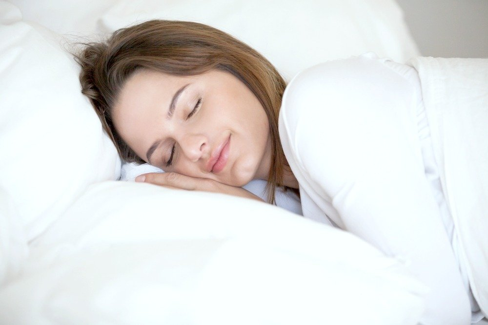 A woman sleeps peacefully on a white pillow and sheets. She uses hypnosis for sleep and sleeps soundly.