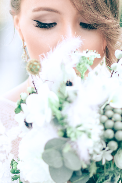 Beautiful bride holds her bouquet close and closes her eyes.
