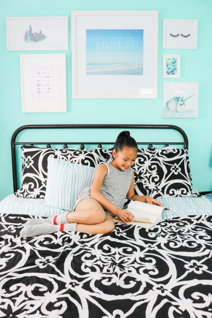 Mimi sits on the bed reading a book. Behind her is a teal wall with her travel-inspired wall art.