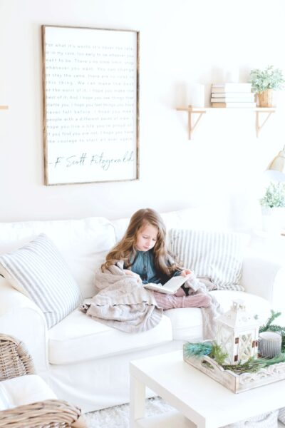 A little girl sits on a couch in her living room. The living room is bright and stylish.