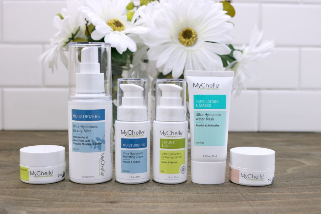 MyChelle Ultra Hyaluronic products. They are natural skincare products lined up on a wooden table, flowers are behind them.