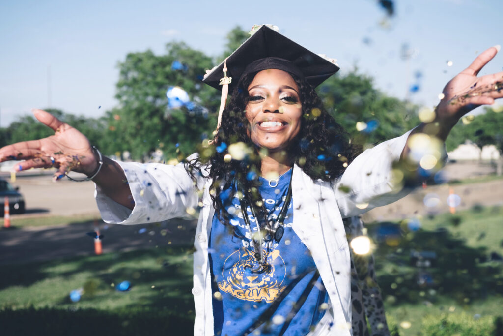 Woman is graduating after forging a career path in healthcare. She is wearing a graduation cap and a stethoscope and throwing glitter in the air.