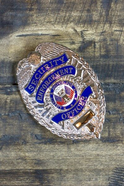 A wooden table with a Security Officer badge on top.