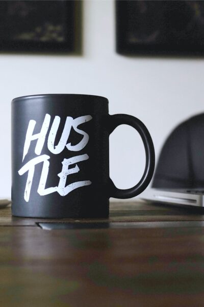 A mug with Hustle written on it sits on a wooden desk.