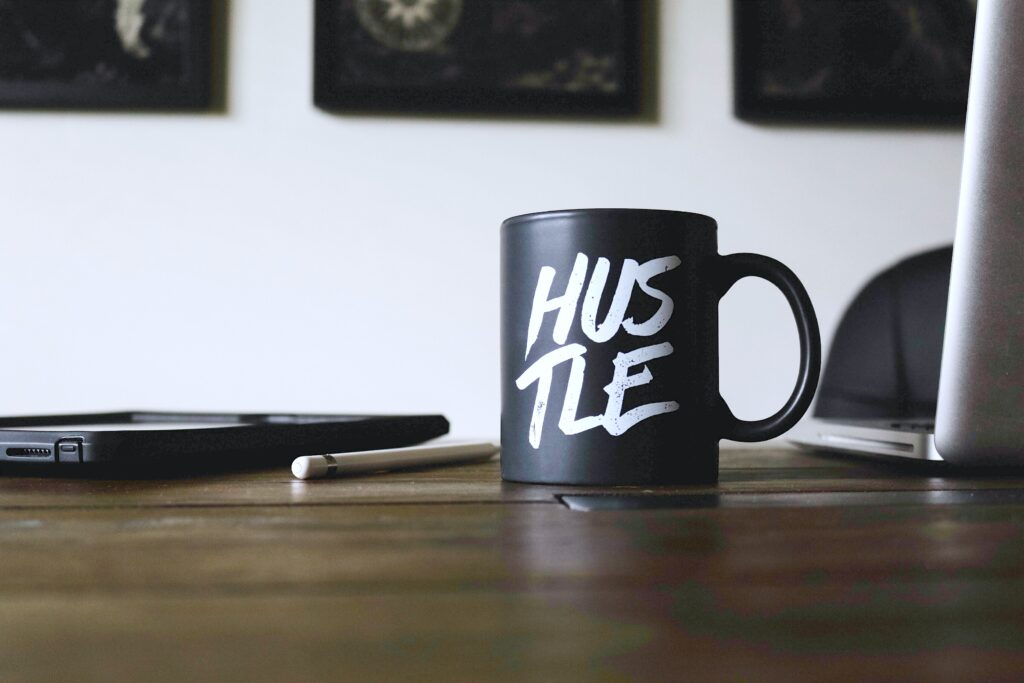 A mug with Hustle written on it sits on a wooden desk. This shows that investing can be a way to earn peace of mind.