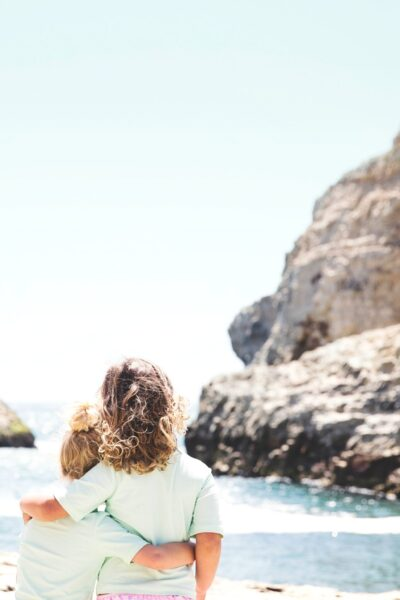 Only the backs of two young sisters are seen as they embrace. Together, they watch the waves of a beautiful seascape.