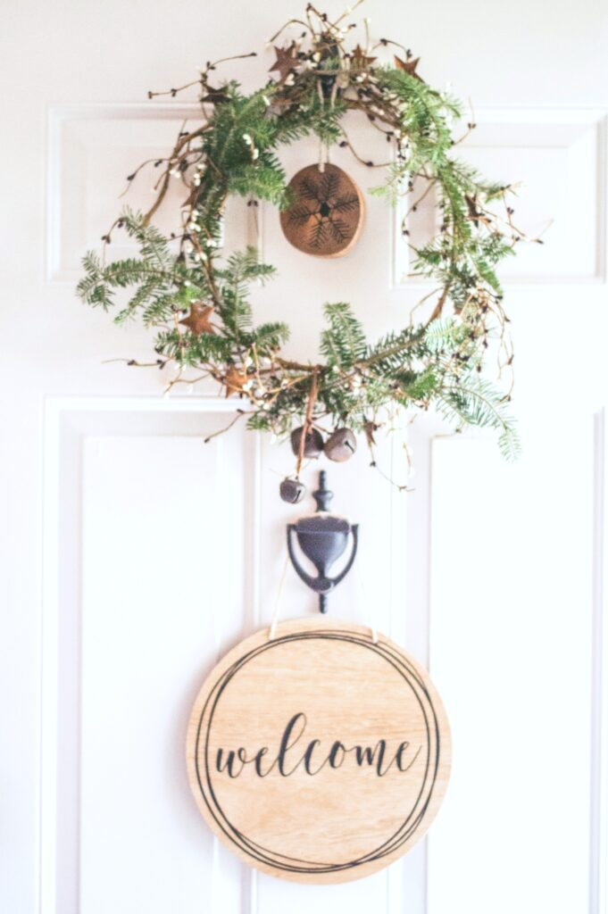 A door with a small wreath and a door knocker. Against the white door, there is a wooden welcome ornament.