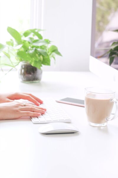 Woman's hand typing on a keyboard and mouse, with a cup of coffee.