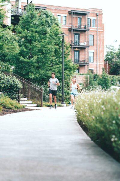 A couple runs through a park.