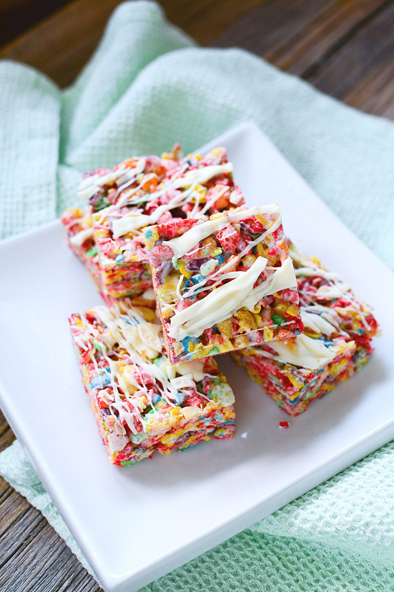 4 Fruity Pebbles Squares on a white plate, atop a green napkin. Treats are placed on a wooden table.