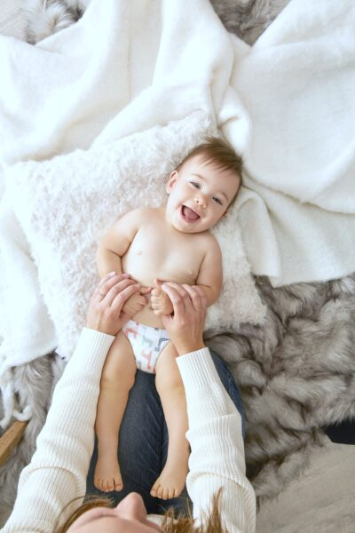 A smiling baby is being tickled by his mom, it is a top view looking down at the baby. He lies on blankets.