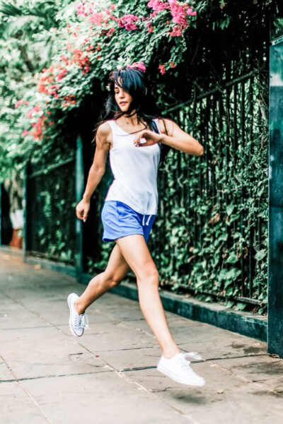 Strong woman running down the street, flowers are behind her, she is midair.