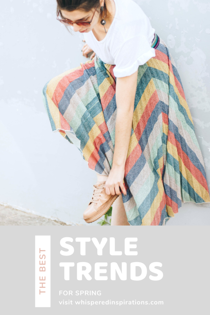 """Woman bends down and touches her shoes. Her style has a b it of vintage yet classic with a tee and sneakers. She doesn't look at the camera. A banner below reads, """"The best style trends for spring."""""""