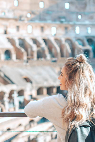 A teenager is pictured with a back back and is smiling with her head turn. In front of her, is a gorgeous stadium. She looks hopeful and happy.