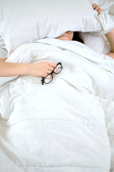 A woman is sick in bed. She is covering her head with a pillow, under her blanket, and is holding her glasses.