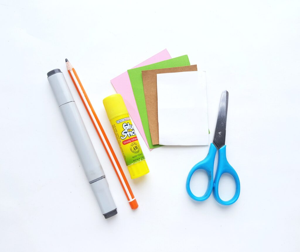A white background with supplies needed for Baby Yoda paper craft. A pair of scissors, marker, pencil, glue stick, and coloured paper.