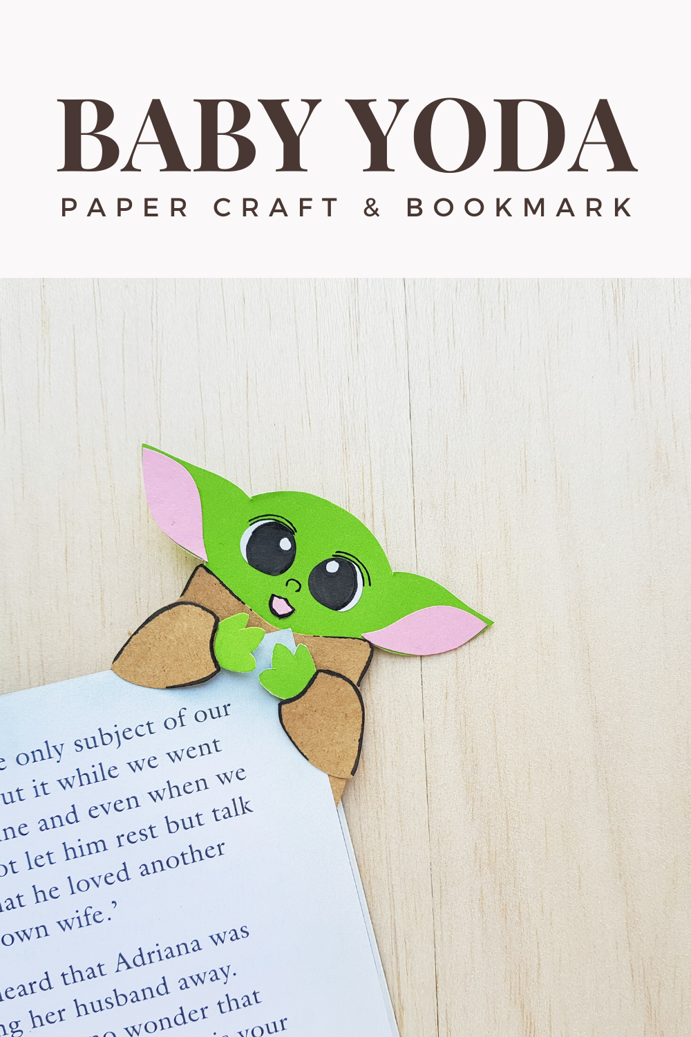 "A banner reads, ""Baby Yoda Paper Craft & Bookmark,"" a picture of the finished Baby Yoda paper craft and bookmark on a corner of a book."