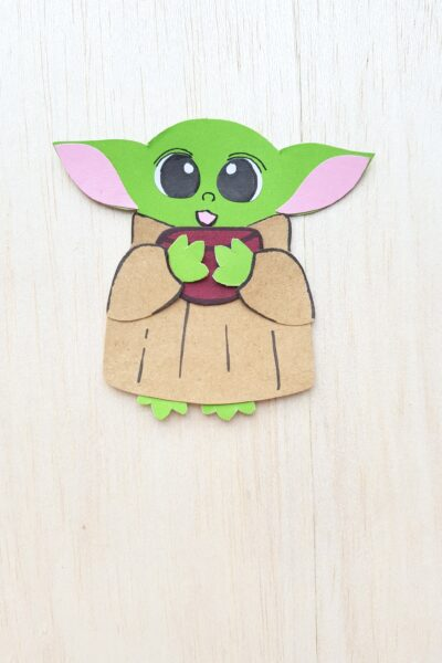 Baby Yoda holding the corner of book, a paper craft used as a bookmark.