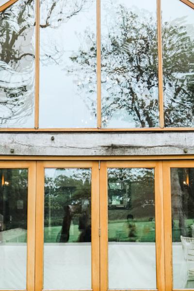 A backyard shows large windows and a wooden bi-fold door.