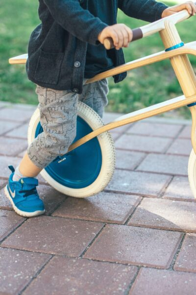 A close up of a little boy with blue Nike shoes, sitting on a wood and blue balance bike.