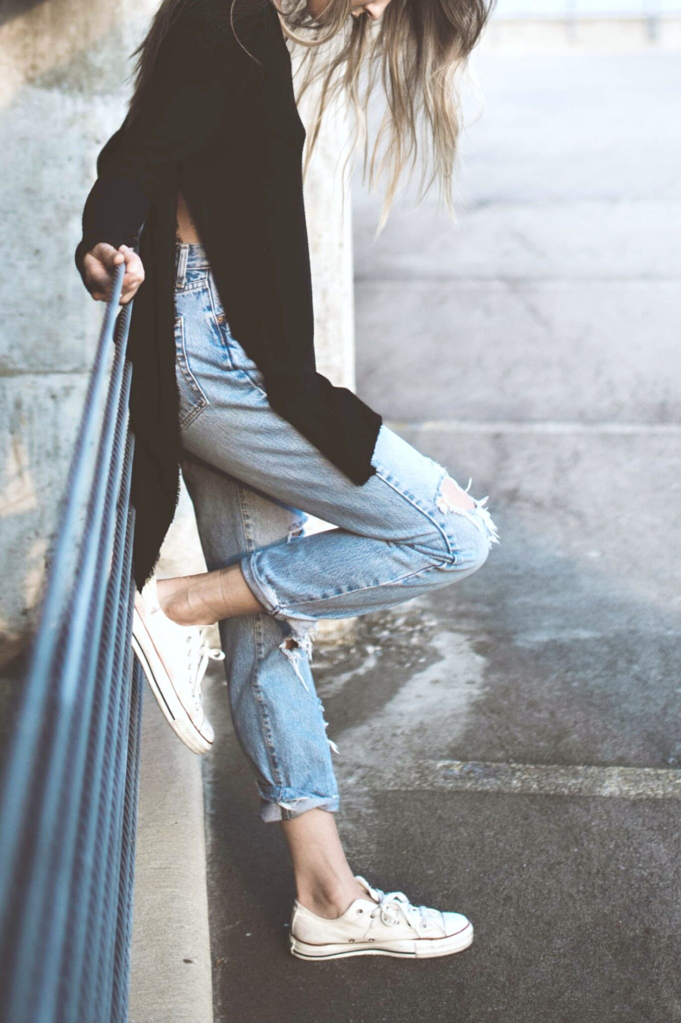 Close up of a trendy girl up against a railing.