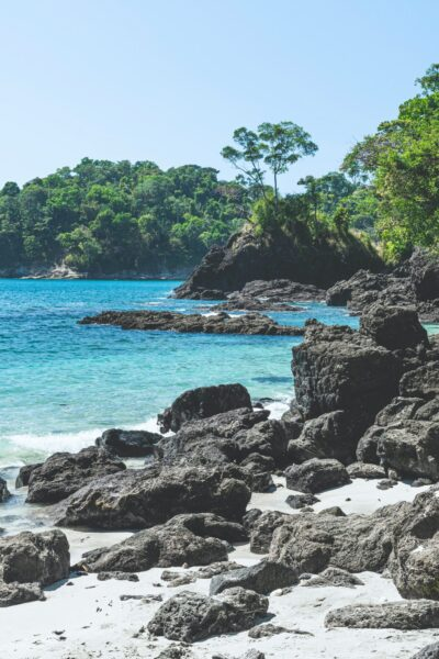 A beautiful beach in Costa Rica, black rocks, white sands, and blue water.
