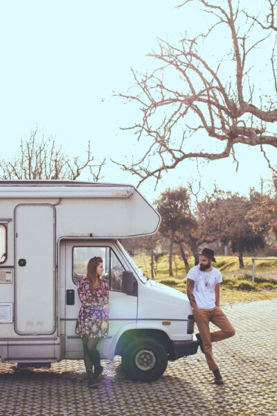 A young, hip, couple lean against their vintage motorhome.