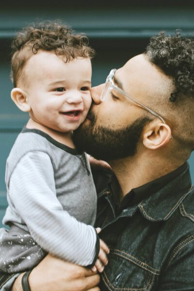 Young Dad kisses his son, against a teal garage.