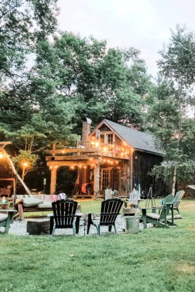 A beautiful backyard with a fire pit and pergola. There are string lights adorning the homes.