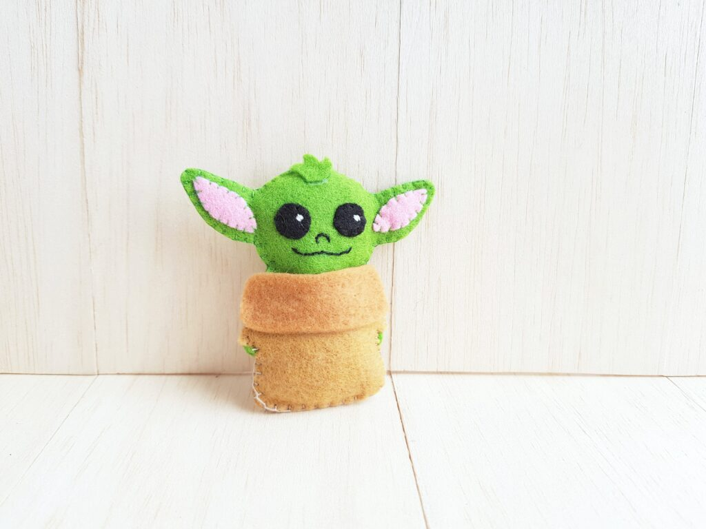 Little Baby Yoda aka The Child is leaning on a wall.