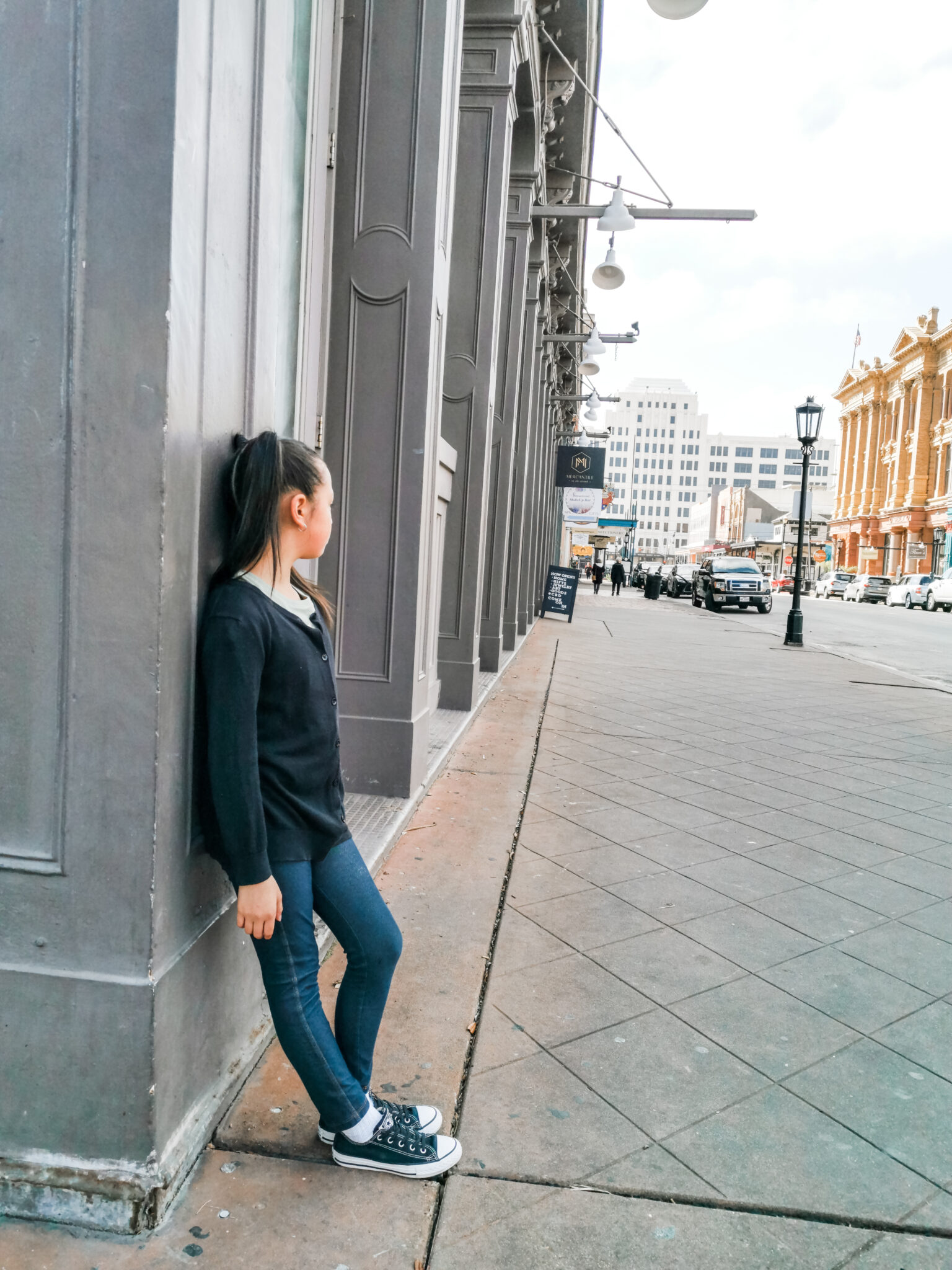 Mimi leans up against a wall by herself, the street is empty and only a few people can be seen at a distance.
