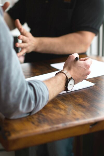 Two people argue over paperwork, their faces are not seen only their hands and the paper work on the table.