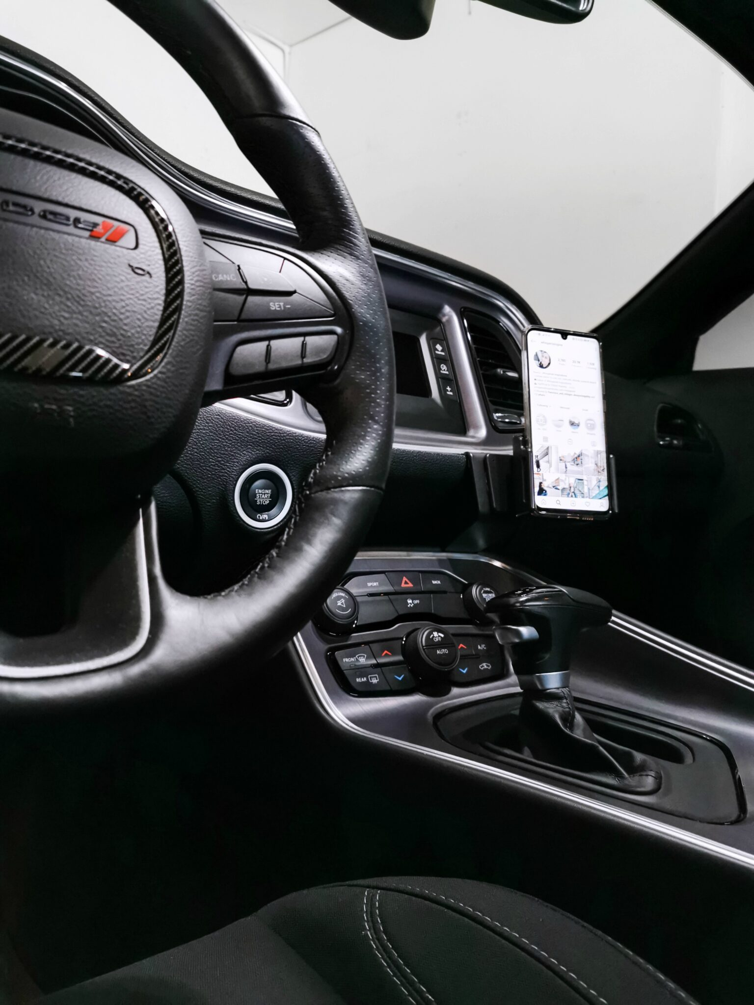 The steering wheel of a 2016 Dodge Challenger. A ProClip adjustable phone holder and mount are shown. The Huawei is inside the holder.