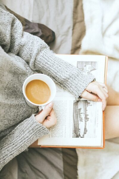Woman reading a book while drinking coffee.