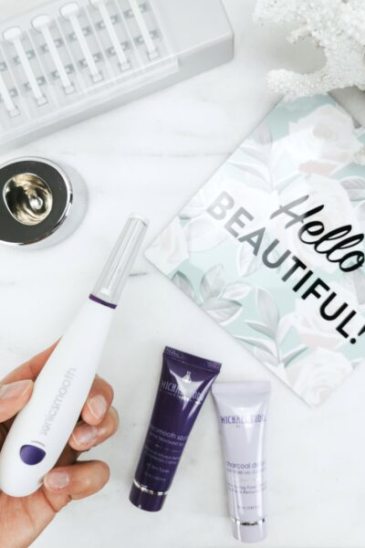 "A hand holding the Sonicsmooth Dermaplaning System, cleanser and treatment, the charger stand, replacement blades, and a sign that says, ""Hello Beautiful, "" is seen."
