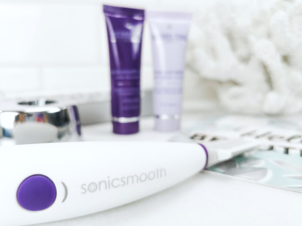 Close up of the Sonicsmooth tool, charging stand, cleanser, and treatment gel. You can see a coral in the background.