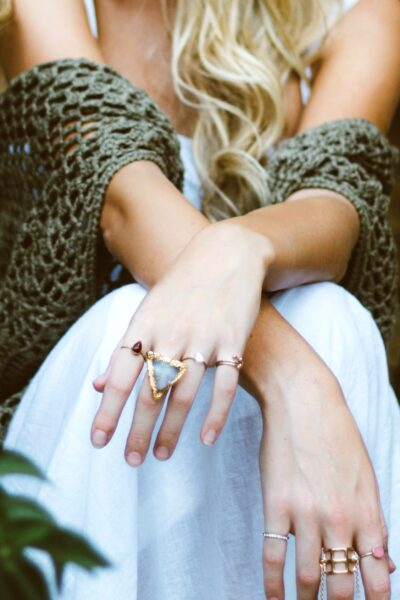 A close up of a woman's arms and skirt, her statement rings are the focus. She has the tips of her blond hair showing.