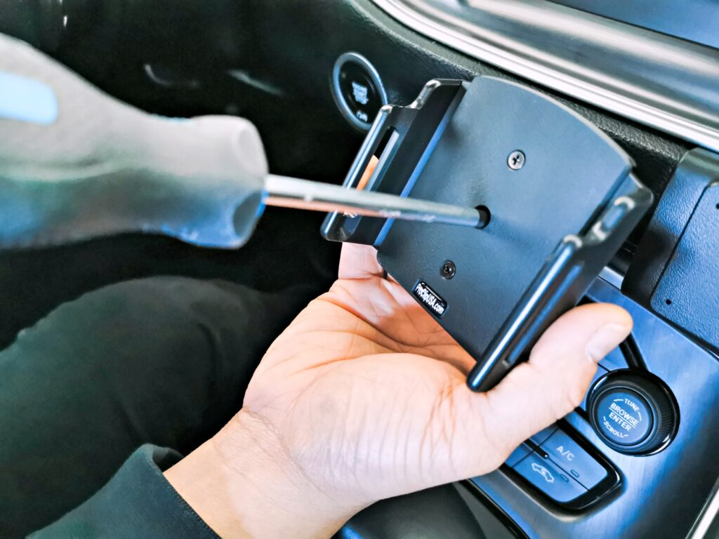 A Philips screwdriver is loosening a screw in the center of phone holder.