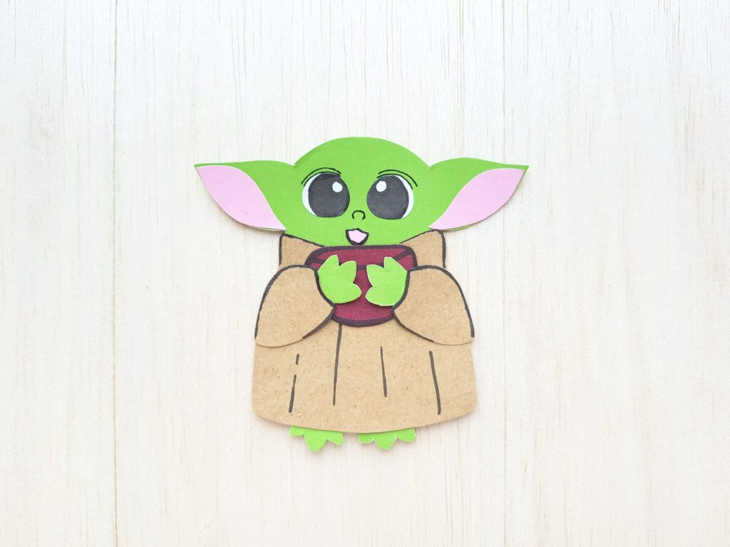 A light wood background with a Baby Yoda made out of coloured paper. He is holding a cup.