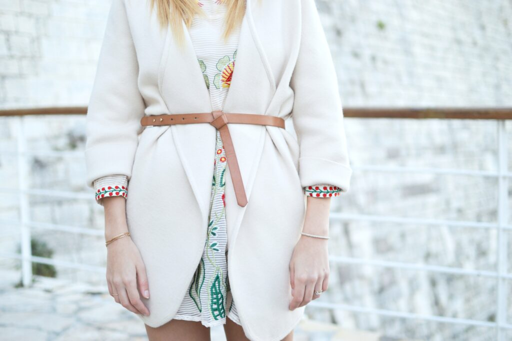 Close up of woman wearing a cardigan and nude belt.