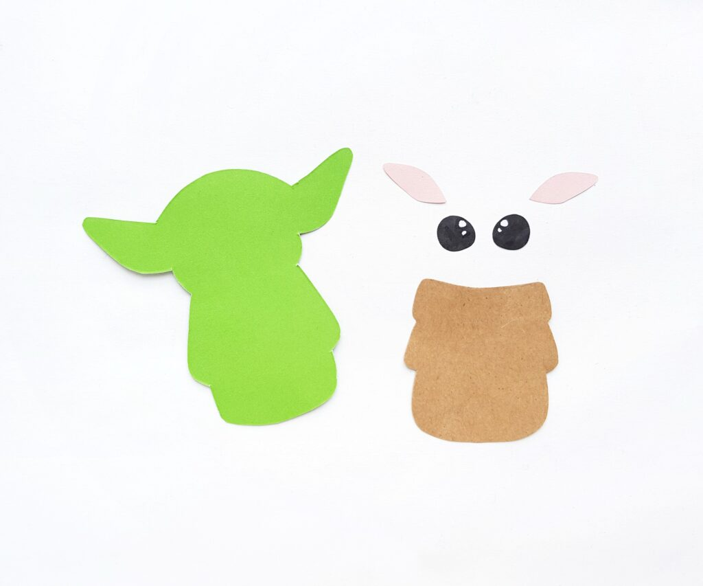 Cardstock paper cut out into Baby Yoda using template.