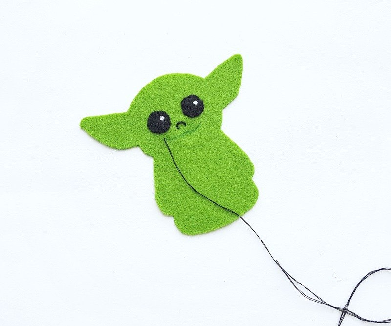 Eyes being sewn onto to Baby Yoda along with nose and mouth.