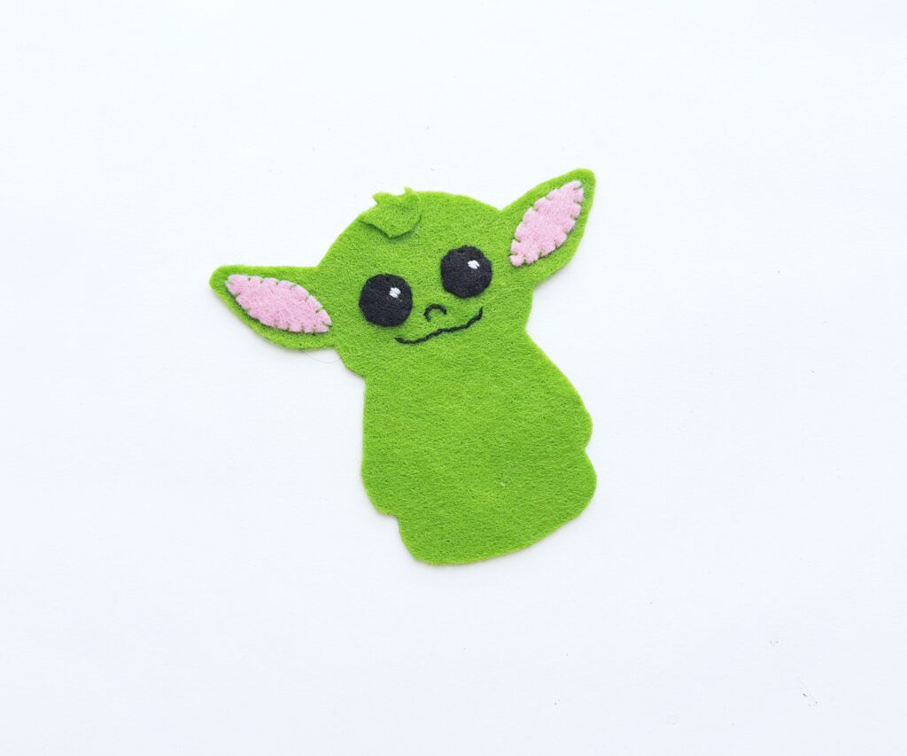 Pink inner ears are sewn onto Baby Yoda's head.