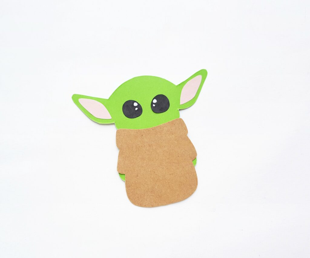 Brown robe is placed onto Baby Yoda body.