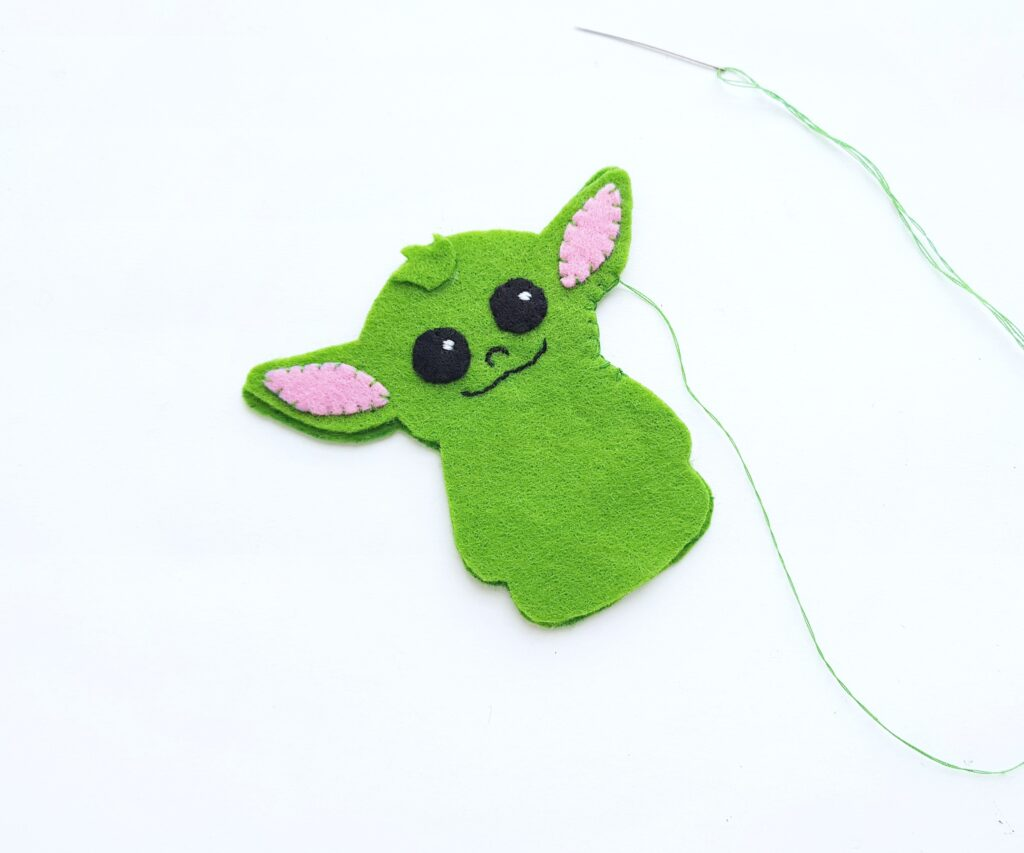 Baby Yoda is being sewn together in preparation for stuffing.