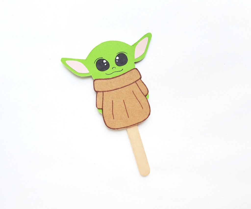 Popsicle stick is attached to Baby Yoda paper craft.