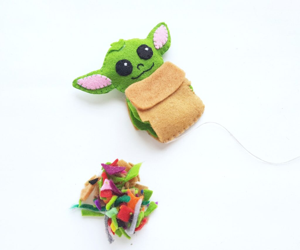 Baby Yoda sewn almost completely and stuffing is waiting to be inserted into plushie.